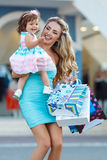 Woman during the shopping with the little girl. Happy family,Mother and her little daughter,go shopping with colored bags together when shopping,family shopping Royalty Free Stock Photos