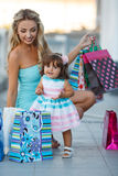 Woman during the shopping with the little girl Stock Image