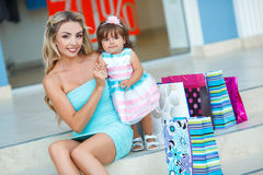 Woman during the shopping with the little girl. Happy family,Mother and her little daughter,go shopping with colored bags together when shopping,family shopping Stock Image