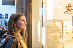 Woman shopping in London and looking at a shop window. Beautiful girl standing and looking at clothes to buy. Lifestyle and shopping concepts Royalty Free Stock Photography