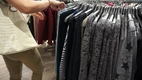 Woman shopping look over dresses on hangers. In fashionable clothes boutique shop stock video footage