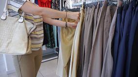 Woman shopping look over dresses on hangers. In fashionable clothes boutique shop stock video