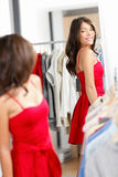 Woman shopping looking in mirror trying clothes dress. In clothing store. Young beautiful multicultural woman trying on red dress in fitting room. Mixed race Royalty Free Stock Images