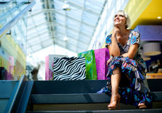 Woman in shopping mall. Attractive woman sitting on the stairs at the shopping mall Stock Photos