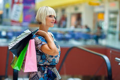 Woman in shopping mall. Attractive woman with bags at the shopping mall escalator stairs Stock Images