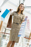 Woman shopping in mall. Carrying bags Stock Photography