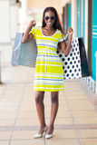 Woman in shopping mall. Happy african woman with shopping bags in mall Stock Photography