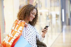 Woman In Shopping Mall Using Mobile Phone Stock Photo