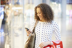 Woman In Shopping Mall Using Mobile Phone Stock Photos