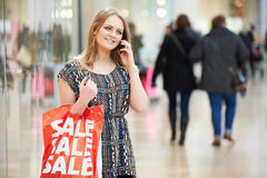 Woman In Shopping Mall Using Mobile Phone. Having A Conversation Royalty Free Stock Images