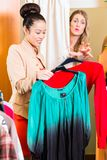 Woman shopping in mall. In front of angry women looking at her selected clothes royalty free stock images