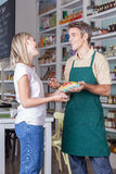 Woman shopping. Man selling a vegetables for a woman Stock Photos