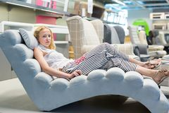 Woman shopping for new sofa chair in furniture store. Stock Images