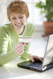 Woman shopping online. Smiling young woman shopping online with credit card and laptop computer Royalty Free Stock Image
