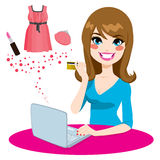 Woman Shopping Online. Beautiful woman shopping online using a laptop buying some fashion goods and products with her golden credit card Royalty Free Stock Images