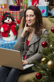 Woman shopping online for Christmas presents. Royalty Free Stock Images