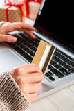 Woman shopping online with a credit card. Christmas online shopping. Female buyer makes order on laptop, closeup of hand with credit card. Woman buys presents Stock Image