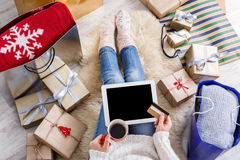 Woman shopping online with a credit card. Christmas online shopping top view. Female buyer touch screen of tablet with copy space, holds credit card. Woman has Royalty Free Stock Images