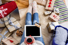 Woman shopping online with a credit card. Christmas online shopping top view. Female buyer touch screen of tablet with copy space, holds credit card. Woman has Royalty Free Stock Photo