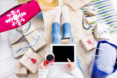Woman shopping online with a credit card. Christmas online shopping top view. Female buyer touch screen of tablet with copy space, holds credit card. Woman has Royalty Free Stock Photography