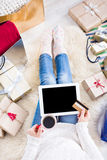 Woman shopping online with a credit card. Christmas online shopping top view. Female buyer touch screen of tablet with copy space, holds credit card. Woman has Stock Photo