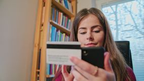 Woman Shopping Online with Credit Card Using Phone. Beautiful woman shopping online with credit card using phone at home. Dolly Shoot. Connected banking app Royalty Free Stock Image