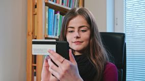 Woman Shopping Online with Credit Card Using Phone. Beautiful woman shopping online with credit card using phone at home. Dolly Shoot. Connected banking app Royalty Free Stock Photography