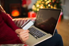 Woman shopping online with laptop at christmas Stock Image