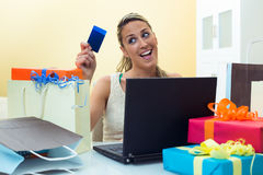 Woman shopping online with laptop looking your credit card. Happy woman shopping online at computer holding credit card and the table full shopping bags Stock Images