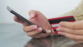 Woman shopping online at smartphone with credit card. Young woman buying goods from the internet and entering number security code from credit card on smartphone Stock Images