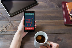 A woman is shopping at the online store. Cart icon. Ecommerce. Royalty Free Stock Images