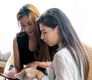 Woman Shopping Online. Two Business Woman Shopping Online by Smartphone or Tablet Pay by Cradit Card Royalty Free Stock Images
