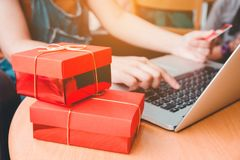 Woman shopping online using laptop with credit card and red gift Stock Images