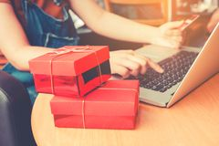 Woman shopping online using laptop with credit card and red gift. Box concept Stock Photo