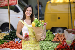 Woman shopping at open street market. Woman shopping at open street market carrying a shopping paper bag full of fruit and vegetables Stock Images