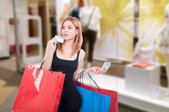 Woman shopping and paying with debit card. Or money while holding gift bags at the mall Royalty Free Stock Photo