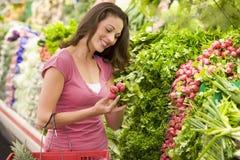 Woman shopping in produce section. Woamn shopping in produce section of supermarket Stock Photography