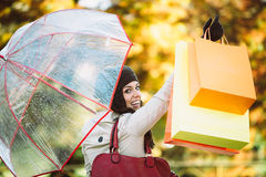 Woman after shopping raising bags in autumn Stock Photos