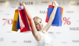 Woman shopping during sales season. Woman rising colorful shopping bags in air, happy that sales season has arrived royalty free stock photo
