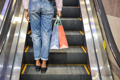 Woman shopping on the scalator in a shopping center Stock Image