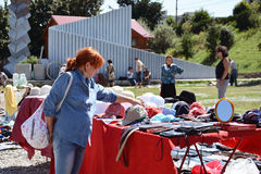 Woman shopping secondhand hats and caps at a flea market. Royalty Free Stock Photography