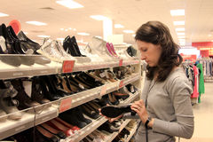 Woman shopping for shoes. Woman shopping in shoes store royalty free stock image