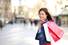 Woman shopping - shopper girl outdoors. Smiling happy holding shopping bags. Portrait of female shopper looking at camera on walking street La Rambla, Barcelona Royalty Free Stock Photos