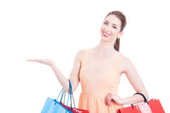 Woman at shopping showing copy space area with hand Stock Photography