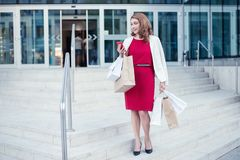 Woman shopping with a smart phone and carrying bags going out of a mall Royalty Free Stock Photography