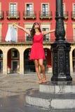 Woman shopping in Spain. Joyful woman dancing after shopping in Spain.  Successful fashion pretty girl raising white bags. Plaza Mayor of Gijon, Asturias, Spain Royalty Free Stock Photos