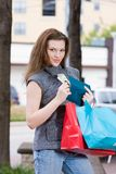 Woman Shopping Spending Limit. Young woman on a shopping trip holding colorful shopping bags, counting her money, thinking about what else she can buy Stock Photography