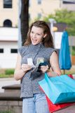 Woman Shopping Spending Limit. Young woman on a shopping trip holding colorful shopping bags, counting her money, thinking about what else she can buy Stock Photos