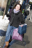 Woman on a shopping spree. Woman running on street on a shopping spree royalty free stock image