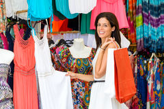 Woman shopping in street summer market. Woman shopping summer colorful dresses and clothes in street market. Tourist shopper looking for bargain clothing and Stock Image